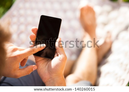 Man using mobile smart phone while relaxing in a hammock - stock photo