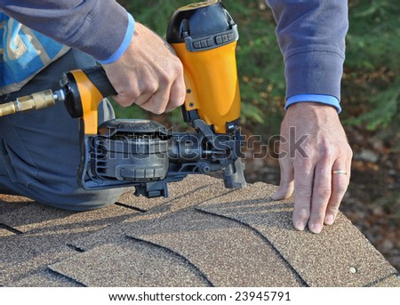 Man using nail gun to attach asphalt shingles to roof - stock photo