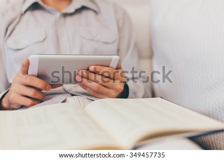 Man using Notes and Tablet. Blurred background.