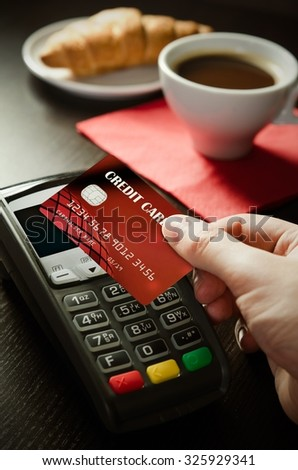 Man using payment terminal with NFC contactless technology in cafeteria - stock photo