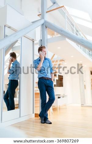 Man using phone in beautiful modern apartment wearing shirt - stock photo
