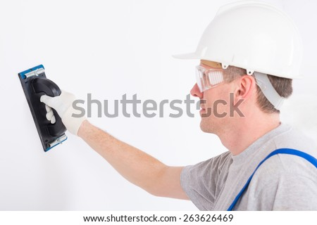 Man using plastering trowel on white wall - stock photo
