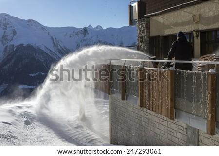 man using powerful snow blower to remove heavy snow from his front yard - stock photo