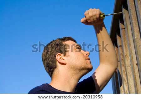 Man using screwdriver to fix porch. Horizontally framed photo. - stock photo