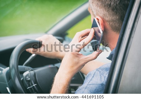 Man using smart phone while driving - stock photo