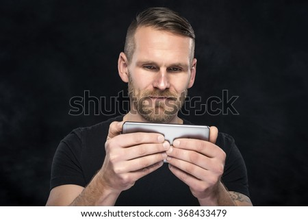 Man using smartphone or tablet pc on dark background. - stock photo