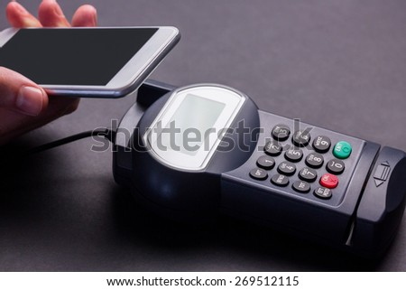 Man using smartphone to express pay against grey background - stock photo