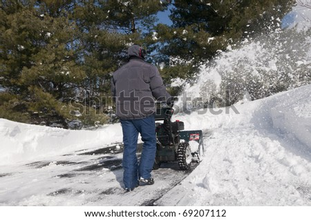 Man using snow blower to clear parking lot and driveway