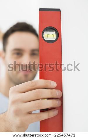 Man using spirit level in new house - stock photo