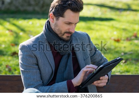 Man using tablet outside in a park. - stock photo