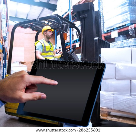 Man using tablet pc against focused driver operating forklift machine - stock photo