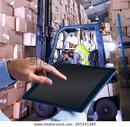 Man using tablet pc against forklift machine in warehouse - stock photo