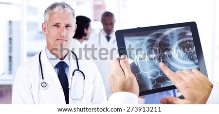 Man using tablet pc against mature doctor pointing at something on his clipboard - stock photo