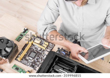 Man using tablet pc during the computer repair. - stock photo
