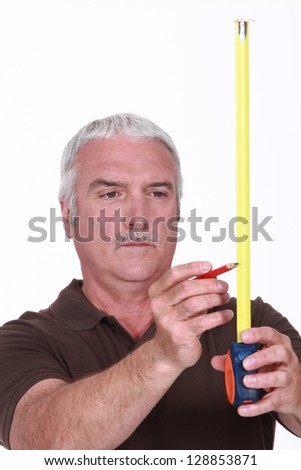 Man using tape measure and pencil - stock photo