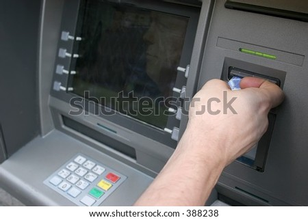 Man using teller machine - Inserts a card