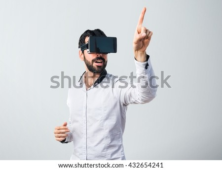 Man using VR glasses touching on transparent screen - stock photo