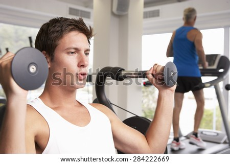 Man Using Weights Machine With Runner On Treadmill In Background