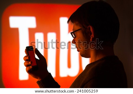 Man using Youtube application on his smartphone, background is an image from the projector - photography from social media meeting in city of Lodz, Poland 07.11. 2014 - stock photo