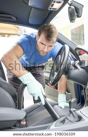 Man vacuuming  the car cabin, cleaning concept.
