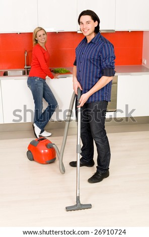 Man vacuuming, woman in background - stock photo