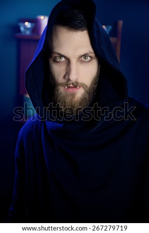 Man vampire with fangs looking camera - stock photo