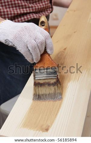 Man varnishing a wood plank - stock photo