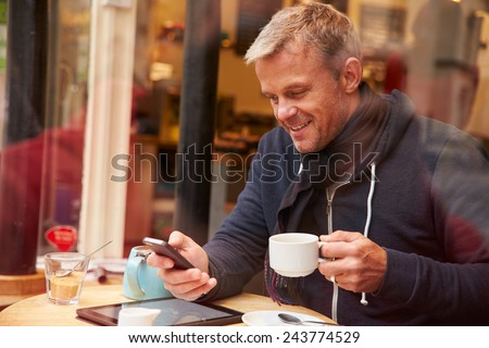 Man Viewed Through Window Of Caf�¢?? Using Mobile Phone - stock photo