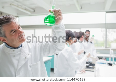 Man viewingliquid while other chemists doing research in the laboratory - stock photo