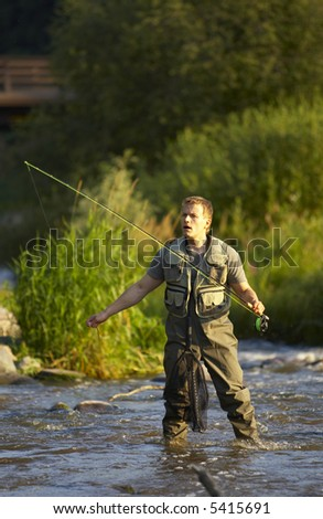 Man wading in a river, fly fishing
