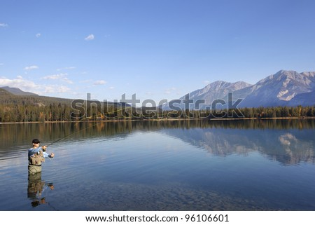 Man waist-deep in water fishing with reflections and mountains in background.