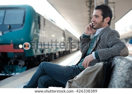 man waiting for the train seated in a train station platform - stock photo