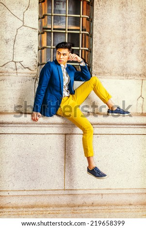 Man Waiting for You. Dressing in blue blazer, yellow pants, casual sneakers, a young handsome guy is sitting by a window on street, turning head, looking away.