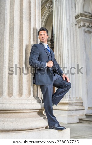 Man waiting for you. Dressing in dark blue three piece suit, necktie, leather shoes, a handsome, sexy, middle age businessman is standing against column outside office, relaxing. Man Formal Fashion. - stock photo