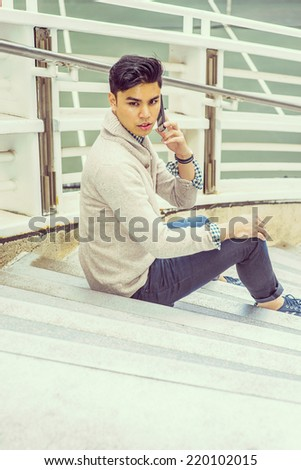 Man waiting for you. Dressing in kitted sweater with shawl collar cardigan, jeans, rolling over cuff, a young guy is sitting on stairs by fence, talking on mobile phone, looking back.   - stock photo