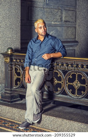 Man Waiting for You. Wearing a blue shirt, gray pants, casual shoes, a young guy with beard, yellow hair is standing by old fashion style railing in a hallway, looking around, relaxing. - stock photo