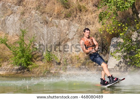Man wakeboarder on pond in park