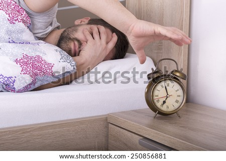 Man wakes up and he is mad at clock ringing - stock photo