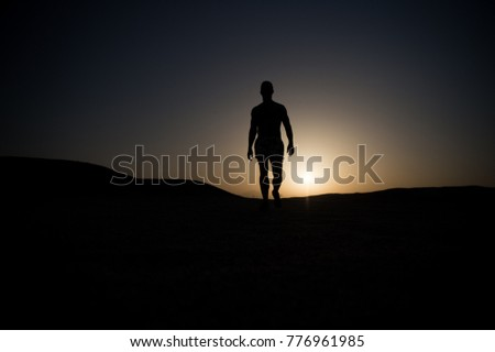 Man walk on sunset sky background. Silhouette of sportsman. Athlete with muscular body in dusk. Sport, fitness, energy, activity concept.