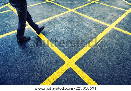 Man walk on wet asphalt street with marked yellow lines.  - stock photo