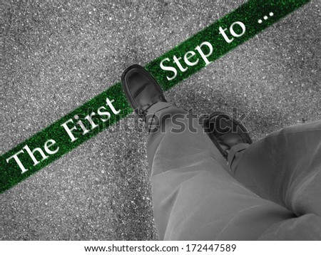 Man walking across a green line with words the first step to - stock photo