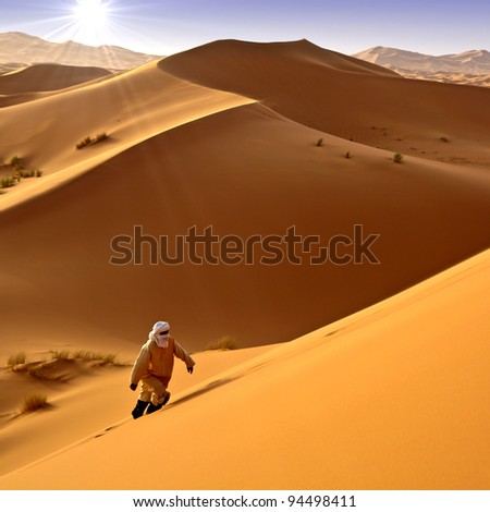 Man walking alone in the desert under the sun. Moroccan background. - stock photo