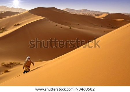 Man walking alone in the sunny desert. Moroccan dunes background. - stock photo