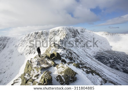man walking along snow and ice covered mountain ridge, helvellyn, lake district - stock photo