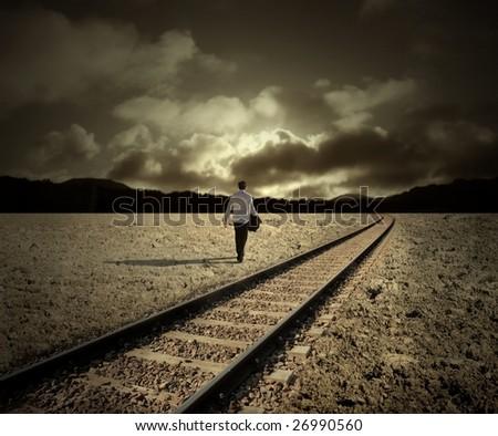 man walking along train tracks - stock photo