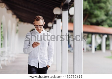 Man walking and reading message on his phone. Modern technology makes it easy to stay connected - stock photo