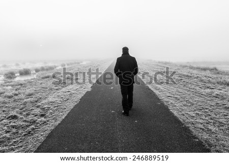Man walking away on an empty desolate raod - stock photo