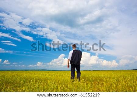 man walking away troughh the filed - stock photo