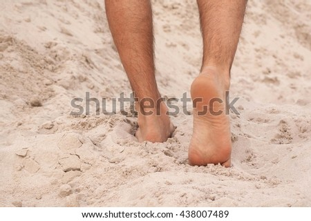 Man walking barefoot in the sand in summer holidays on beach - stock photo