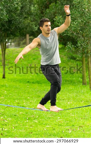 Man walking barefoot on slackline in park with arms out and deep concentrated facial expression. - stock photo